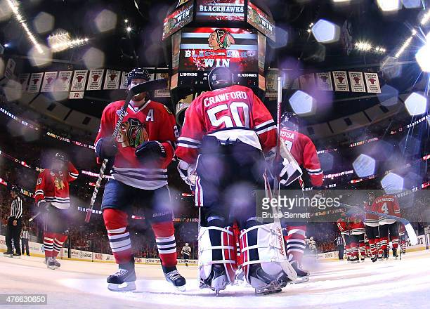 Corey Crawford of the Chicago Blackhawks celebrates with his teammates after defeating the Tampa Bay Lightning 2 to 1 in Game Four of the 2015 NHL...