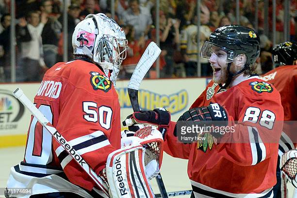 Corey Crawford of the Chicago Blackhawks celebrates with teammate Patrick Kane after defeating the Boston Bruins in Game Five of the 2013 NHL Stanley...
