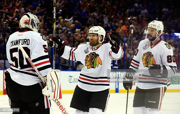 Corey Crawford of the Chicago Blackhawks celebrates with teammates Antoine Vermette and Kimmo Timonen after defeating the Tampa Bay Lightning by a...