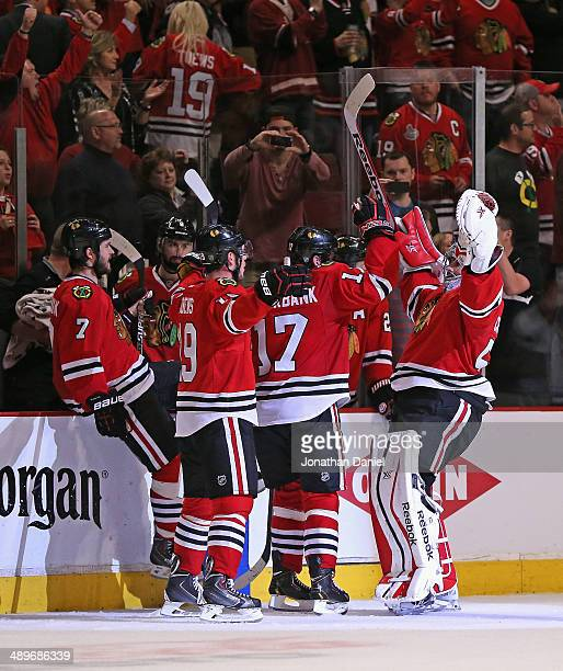Corey Crawford of the Chicago Blackhawks celebrates with teammates including Brent Seabrook Jonathan Toews and Sheldon Brookbank after a win over the...