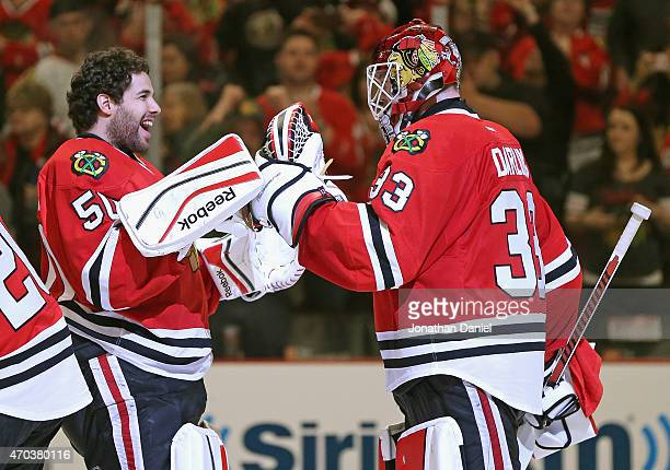 Corey Crawford of the Chicago Blackhawks congratulates Scott Darling after a win over the Nashville Predators in Game Three of the Western Conference...