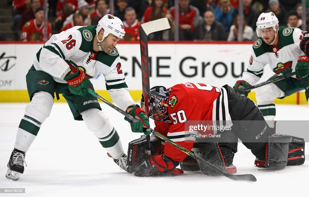 Corey Crawford #50 of the Chicago Blackhawks covers the puck behind Daniel Winnik #26 of the Minnesota Wild at the United Center on December 17, 2017 in Chicago, Illinois.