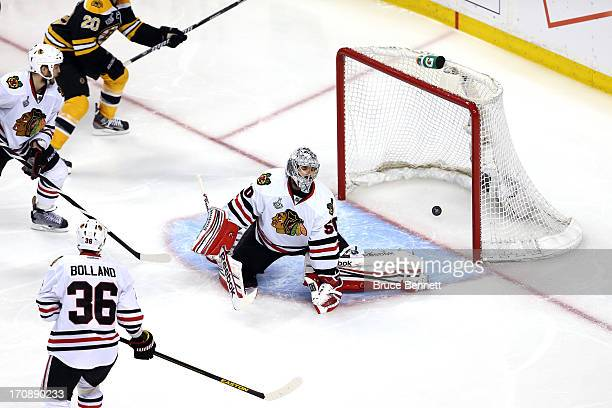 Corey Crawford of the Chicago Blackhawks fails to make a save on a shot by Patrice Bergeron of the Boston Bruins during the third period in Game Four...