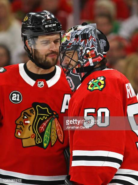Corey Crawford of the Chicago Blackhawks gets a laugh from a conversation with Brett Seabrook during a game against the Arizona Coyotes at the United...