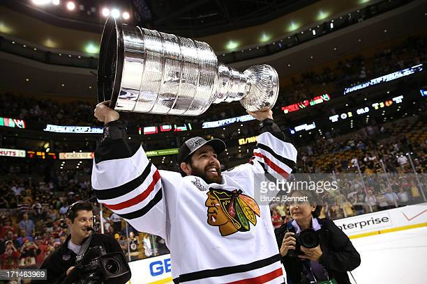 Corey Crawford of the Chicago Blackhawks hoists the Stanley Cup Trophy after defeating the Boston Bruins in Game Six of the 2013 NHL Stanley Cup...