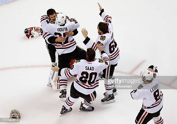 Corey Crawford of the Chicago Blackhawks is mobbed by teammates including Johnny Oduya Brandon Saad Andrew Shaw and Nick Leddy after winning 32...