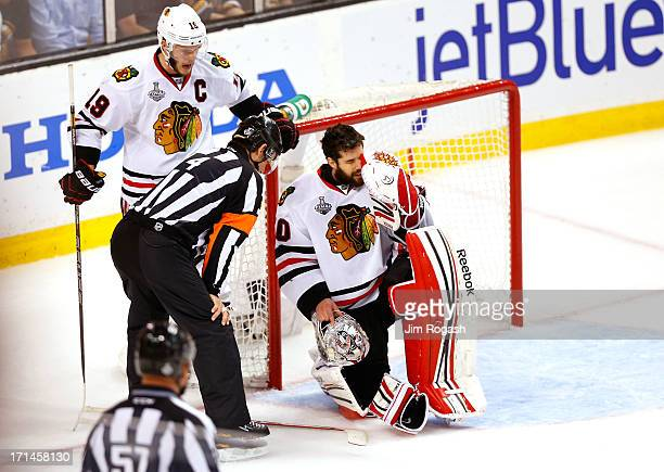 Corey Crawford of the Chicago Blackhawks kneels on the ice after being hit with a puck against the Boston Bruins in Game Six of the 2013 NHL Stanley...