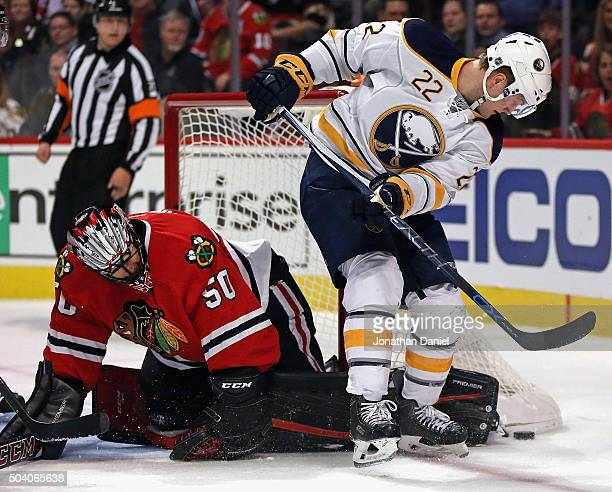 Corey Crawford of the Chicago Blackhawks knocks the puck away from Johan Larsson of the Buffalo Sabres at the United Center on January 8 2016 in...
