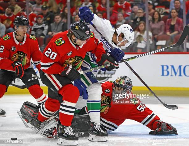 Corey Crawford of the Chicago Blackhawks knocks the puck away on a shot by Loui Eriksson of the Vancouver Canucks as Brandon Saad defends at the...