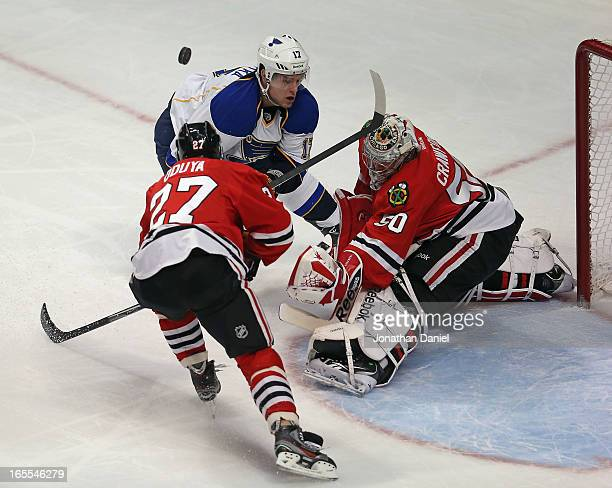 Corey Crawford of the Chicago Blackhawks knocks the puck away on a shot by Vladimir Sobotka of the St Louis Blues as Johnny Oduya defends at the...