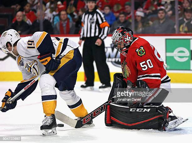 Corey Crawford of the Chicago Blackhawks knocks the puck back through the legs of Calle Jarnkrok of the Nashville Predators at the United Center on...