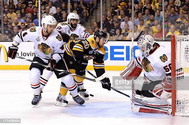 Corey Crawford of the Chicago Blackhawks makes a save against Daniel Paille of the Boston Bruins in Game Six of the 2013 NHL Stanley Cup Final at TD...