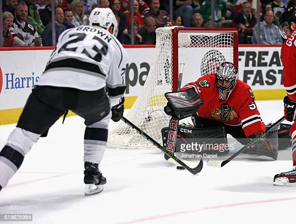 Corey Crawford of the Chicago Blackhawks makes a save against Dustin Brown of the Los Angeles Kings at the United Center on March 14 2016 in Chicago...