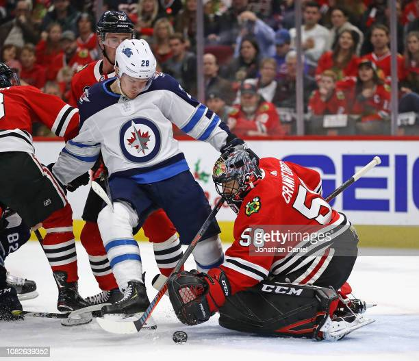 Corey Crawford of the Chicago Blackhawks makes a save against Jack Roslovic of the Winnipeg Jets at the United Center on December 14 2018 in Chicago...