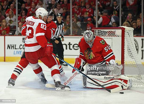 Corey Crawford of the Chicago Blackhawks makes a save against Johan Franzen of the Detroit Red Wings as Klas Dahlbeck defends during a preseason game...