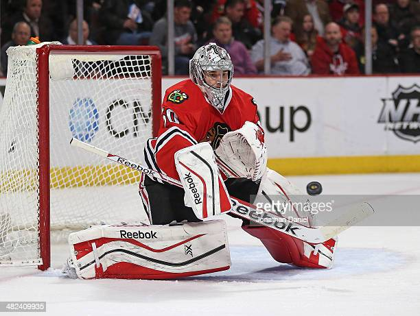 Corey Crawford of the Chicago Blackhawks makes a save against the Minnesota Wild at the United Center on April 3 2014 in Chicago Illinois