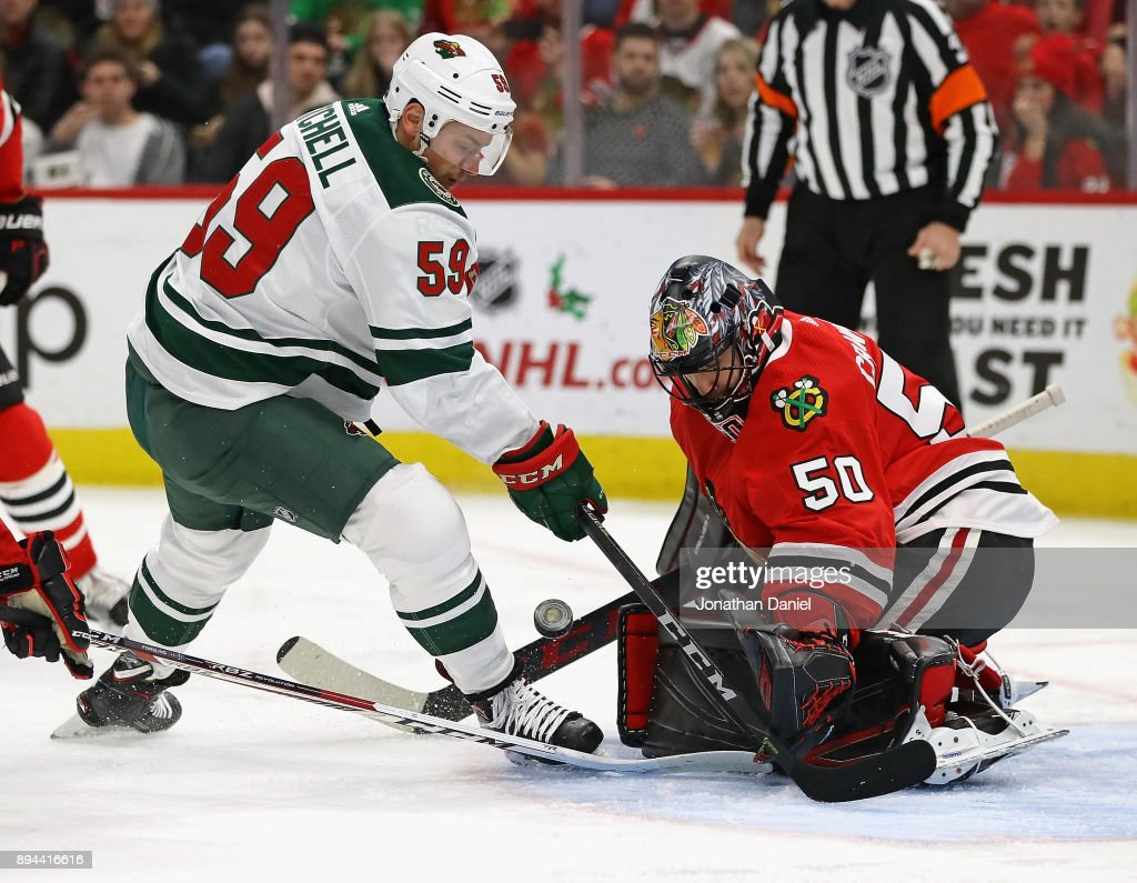 Corey Crawford #50 of the Chicago Blackhawks makes a save against Zack Mitchell #59 of the Minnesota Wild at the United Center on December 17, 2017 in Chicago, Illinois.