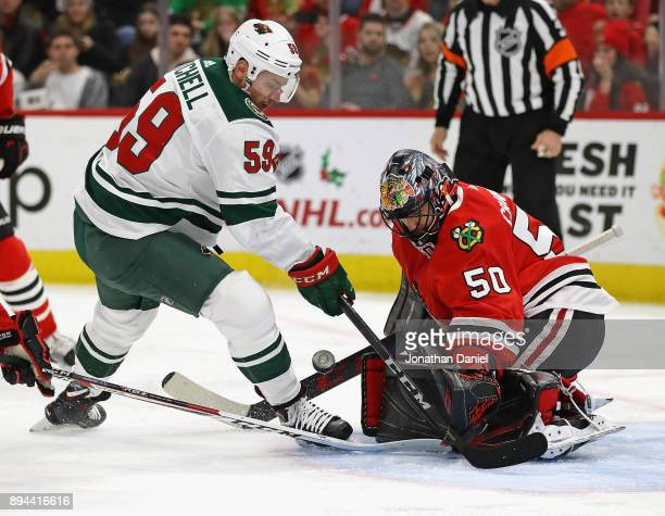 Corey Crawford of the Chicago Blackhawks makes a save against Zack Mitchell of the Minnesota Wild at the United Center on December 17 2017 in Chicago...