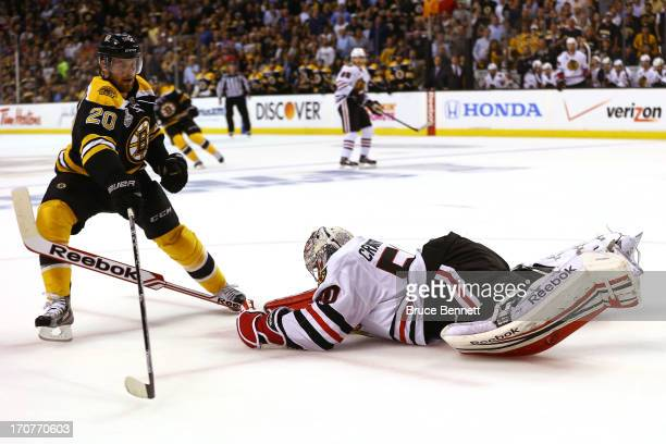 Corey Crawford of the Chicago Blackhawks makes a save in the first period against Daniel Paille of the Boston Bruins in Game Three of the 2013 NHL...