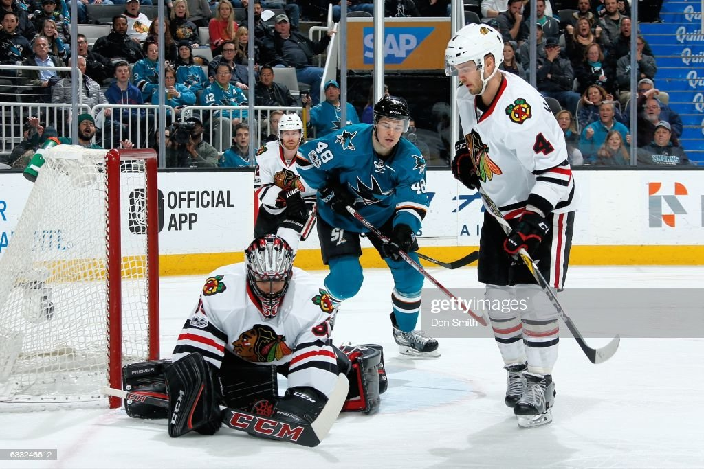Corey Crawford #50 of the Chicago Blackhawks makes a save while Tomas Hertl #48 of the San Jose Sharks and Niklas Hjalmarsson #4 of the Chicago Blackhawks look at SAP Center at San Jose on January 31, 2017 in San Jose, California.