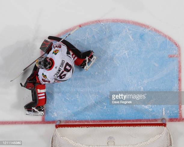 Corey Crawford of the Chicago Blackhawks reacts to a shot against the Detroit Red Wings during an NHL game at Little Caesars Arena on March 6, 2020...
