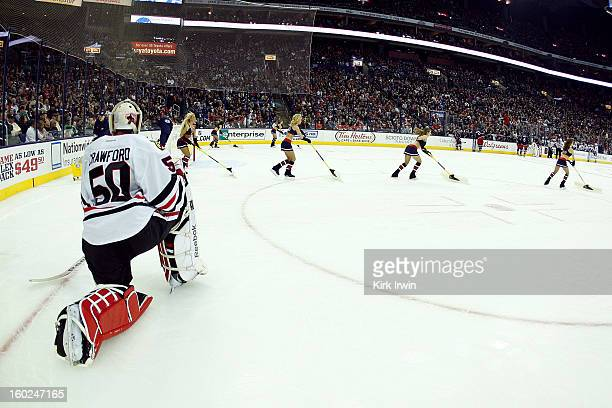 Corey Crawford of the Chicago Blackhawks rests while the ice crew cleans the ice during a stoppage in the game against the Columbus Blue Jackets on...