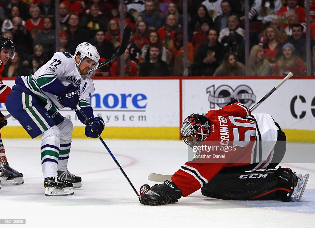 Corey Crawford #50 of the Chicago Blackhawks stops a shot by Daniel Sedin #22 of the Vancouver Canucks at the United Center on January 22, 2017 in Chicago, Illinois.