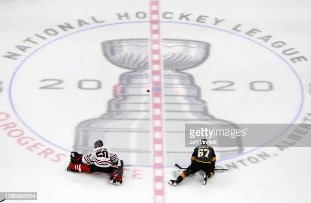 Corey Crawford of the Chicago Blackhawks stretches along with Max Pacioretty of the Vegas Golden Knights before the start of Game One of the Western...