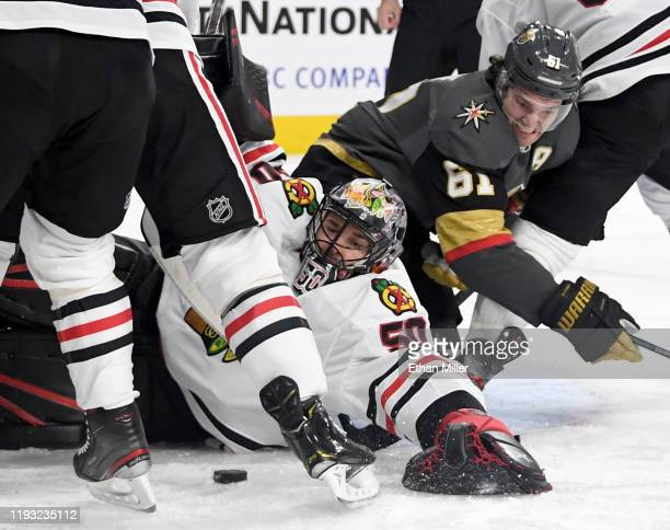 Corey Crawford of the Chicago Blackhawks tries to cover the puck as he defends the net against Mark Stone of the Vegas Golden Knights in the second...