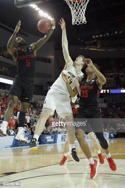 Corey Davis Jr #5 and Fabian White Jr #35 of the Houston Cougars rebound against Jon Teske of the Michigan Wolverines in the second half during the...
