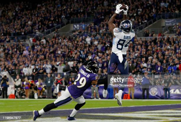 Corey Davis of the Tennessee Titans catches a touchdown pass from Derrick Henry over Earl Thomas of the Baltimore Ravens in the third quarter of the...