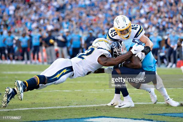 Corey Davis of the Tennessee Titans catches a touchdown pass in between Drue Tranquill and Denzel Perryman of the Los Angeles Chargers at Nissan...
