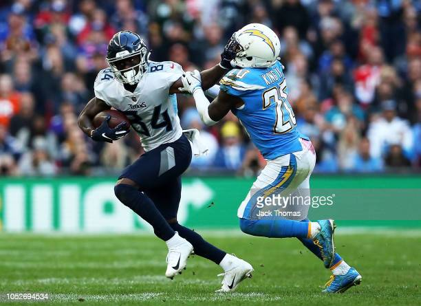 Corey Davis of the Tennessee Titans fends off Desmond King of the Los Angeles Chargers during the NFL International Series game between Tennessee...