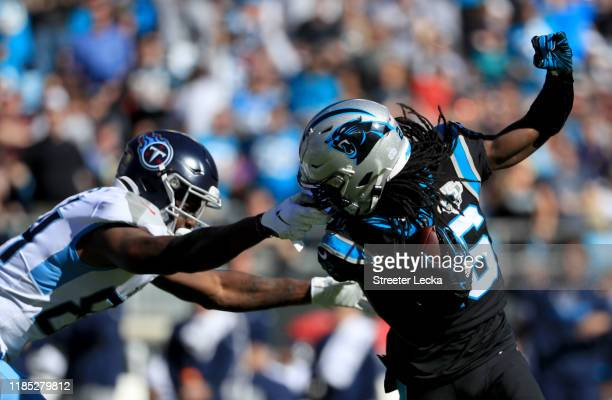 Corey Davis of the Tennessee Titans grabs the facemask of Donte Jackson of the Carolina Panthers after an interception by Jackson during their game...
