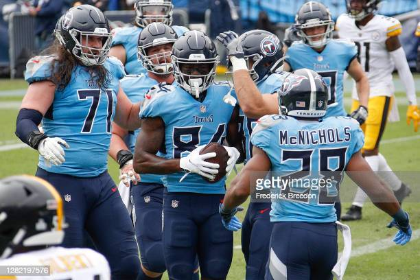 Corey Davis of the Tennessee Titans is congratulated by teammates after scoring a touchdown against the Pittsburgh Steelers during the first half at...