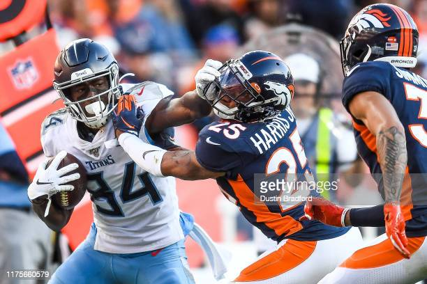 Corey Davis of the Tennessee Titans is pushed toward the sideline by Chris Harris of the Denver Broncos in the fourth quarter at Empower Field at...
