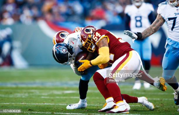 Corey Davis of the Tennessee Titans is tackled by Ha Ha Clinton-Dix of the Washington Redskins and Mason Foster while running with the ball during...