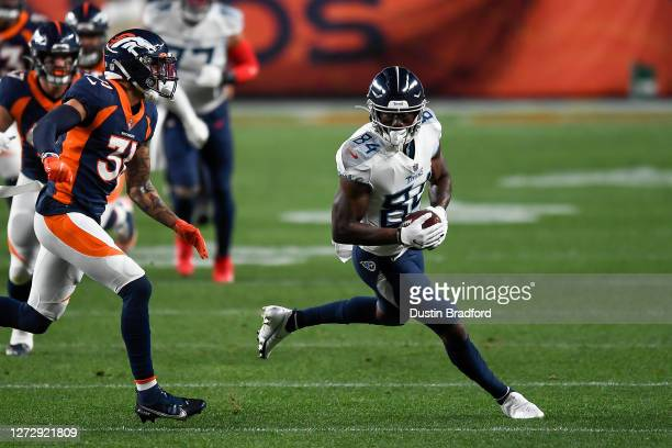 Corey Davis of the Tennessee Titans runs after a catch as Justin Simmons of the Denver Broncos covers the play during a game at Empower Field at Mile...
