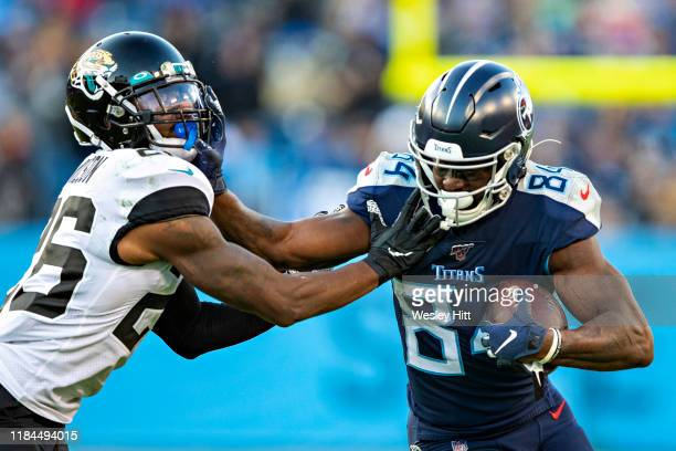 Corey Davis of the Tennessee Titans runs the ball after catching a pass and stiff arms Jarrod Wilson of the Jacksonville Jaguars at Nissan Stadium on...