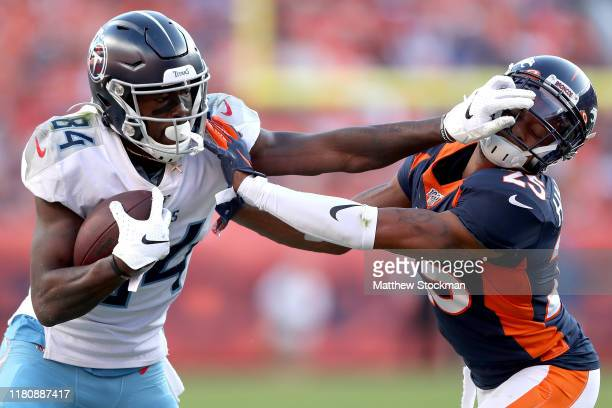 Corey Davis of the Tennessee Titans stiff arms Chris Harris Jr of the Denver Broncos after making a reception in the fourth quarter at Broncos...