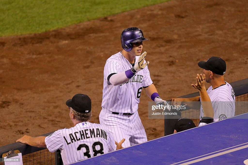 Corey Dickerson #6 of the Colorado Rockies celebrates at the top of the dugout after hitting a two-run home run during the fourth inning against the Los Angeles Dodgers at Coors Field on September 16, 2014 in Denver, Colorado.