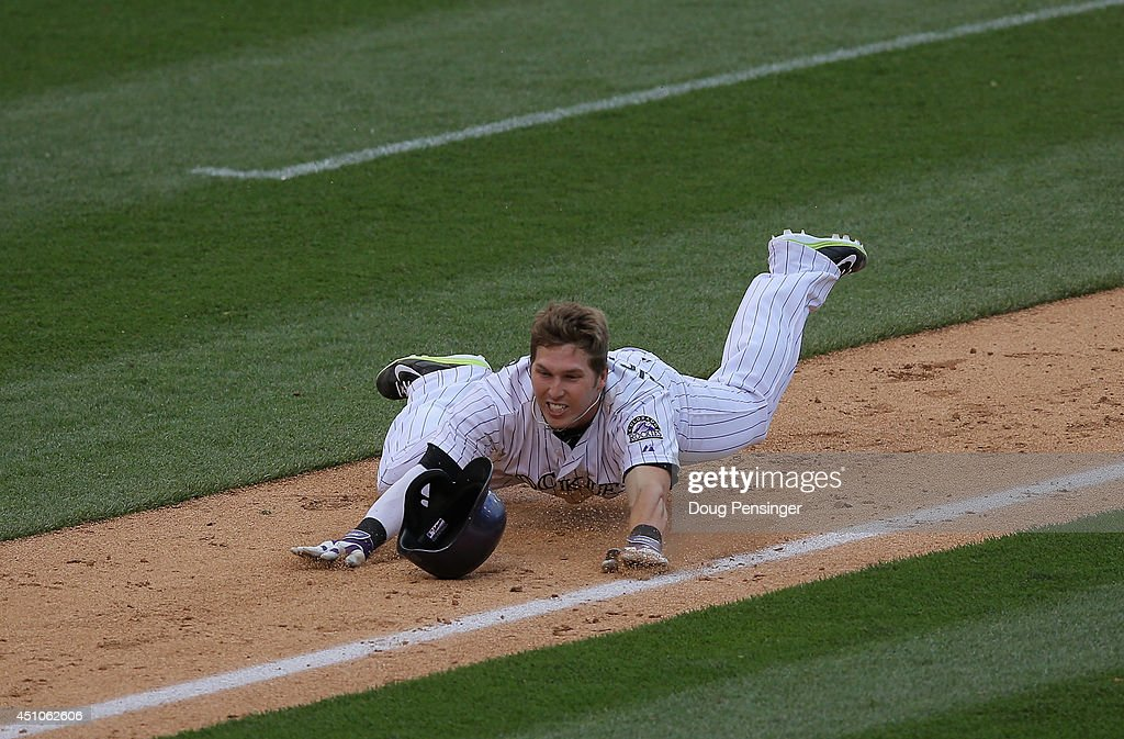 Corey Dickerson #6 of the Colorado Rockies falls and is tagged out as he tries to advance home on his triple off of Francisco Rodriguez #57 of the Milwaukee Brewers in the ninth inning at Coors Field on June 22, 2014 in Denver, Colorado. The Brewers defeated the Rockies 6-5.