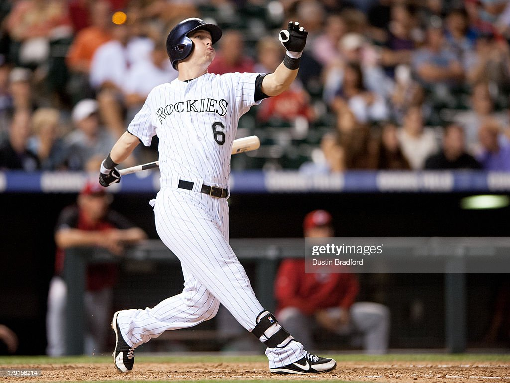 Corey Dickerson #6 of the Colorado Rockies follows through on an eighth inning two run home run against the Cincinnati Reds during a game at Coors Field on August 31, 2013 in Denver, Colorado. The Reds beat the Rockies 8-3.