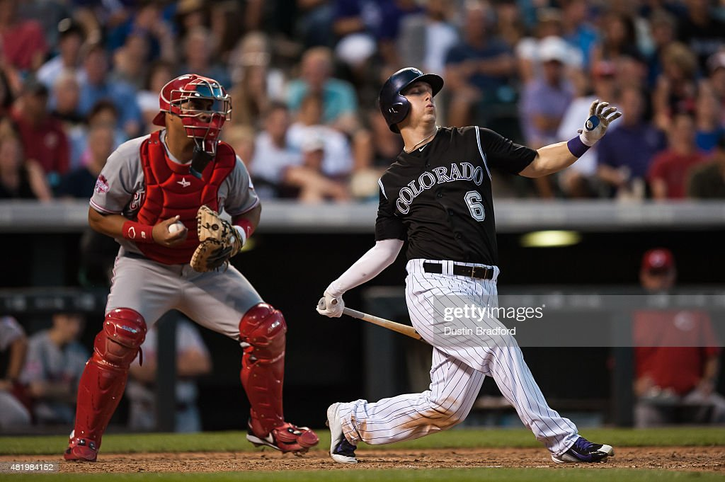 Corey Dickerson #6 of the Colorado Rockies misses on a big swing for a strikeout for the third out of the seventh inning as Brayan Pena #29 of the Cincinnati Reds catches during a game at Coors Field on July 25, 2015 in Denver, Colorado.