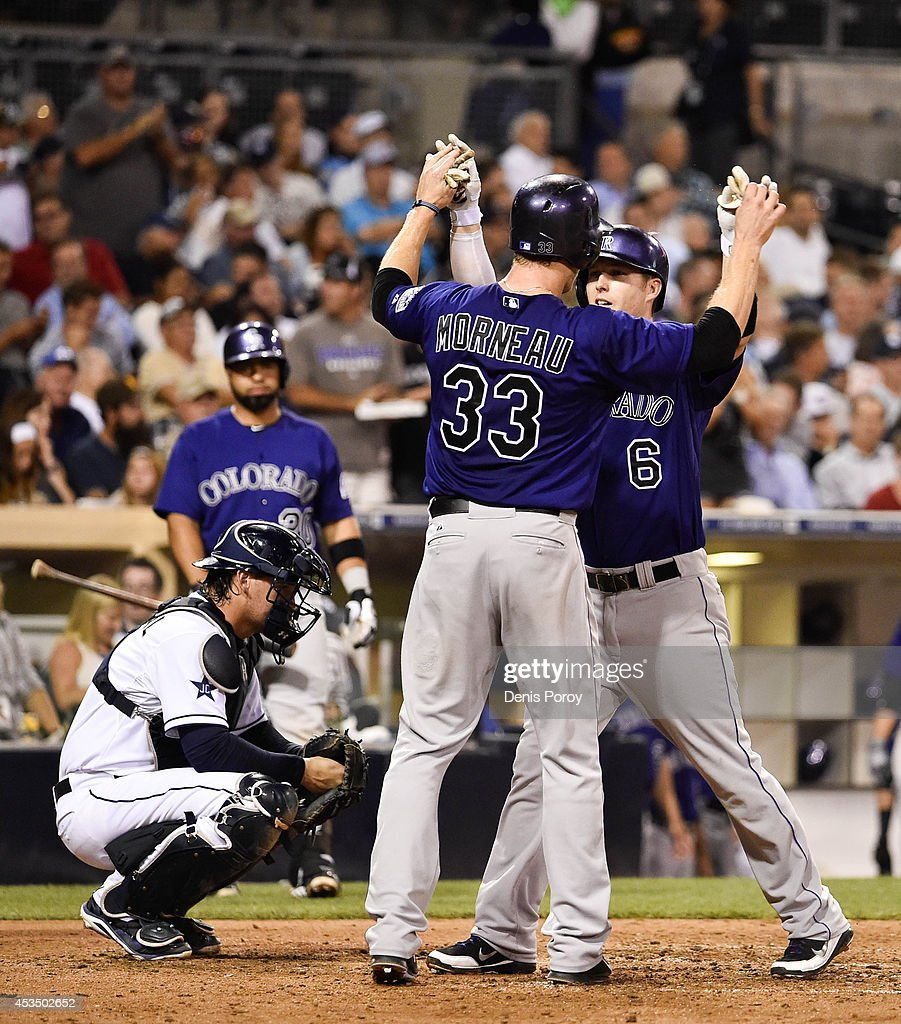 Corey Dickerson #6 of the Colorado Rockies, right, is congratulated by Justin Morneau #33 after he hit a three run home run during the sixth inning of a baseball game against the San Diego Padres at Petco Park August, 11, 2014 in San Diego, California.