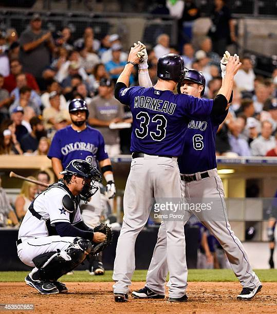 Corey Dickerson of the Colorado Rockies right is congratulated by Justin Morneau after he hit a three run home run during the sixth inning of a...
