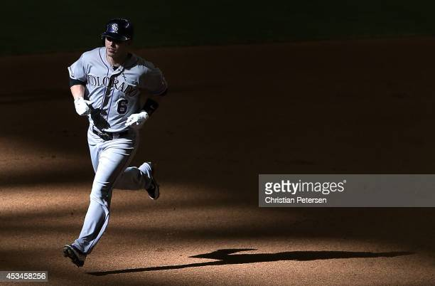Corey Dickerson of the Colorado Rockies rounds the bases after hitting a solo home run against the Arizona Diamondbacks during the tenth inning of...