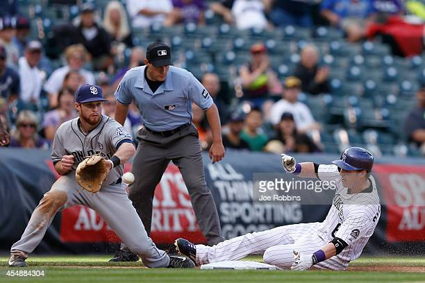Corey Dickerson of the Colorado Rockies slides at third base ahead of the throw to Cory Spangenberg of the San Diego Padres in the seventh inning of...