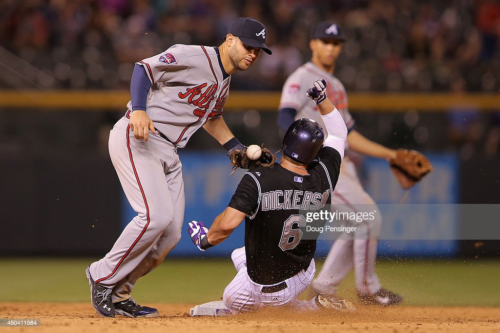 Corey Dickerson #6 of the Colorado Rockies slides safely into second with a stolen base as second baseman Tommy La Stella #7 of the Atlanta Braves fails to keep the ball in his glove in the eighth inning at Coors Field on June 10, 2014 in Denver, Colorado.