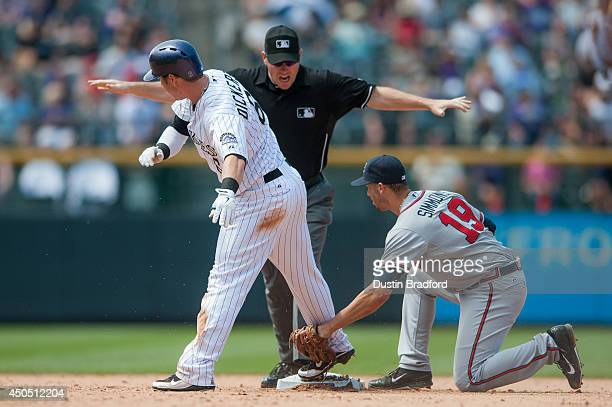 Corey Dickerson of the Colorado Rockies slides safely into second base with a double as Andrelton Simmons of the Atlanta Braves attempts a tag and...